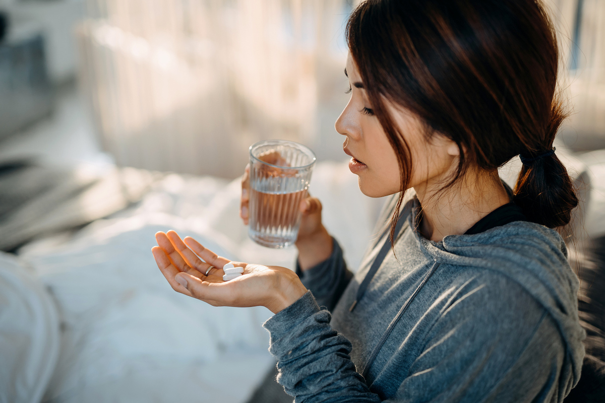 Young woman sitting on bed and feeling sick, taking medication in hand with a glass of water
