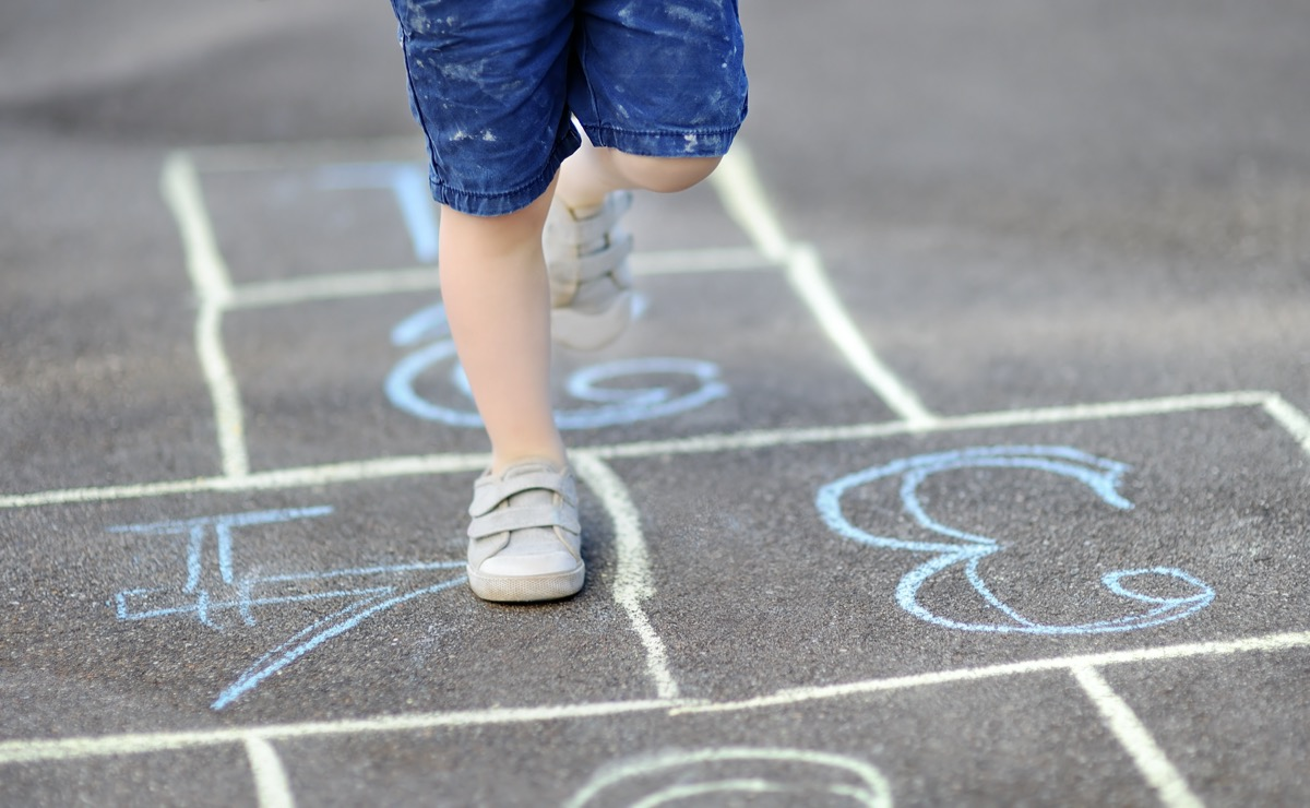 Close-up on the feet of a child playing hopscotch