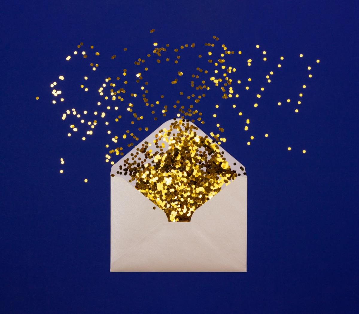 Envelope full of gold glitter against blue background