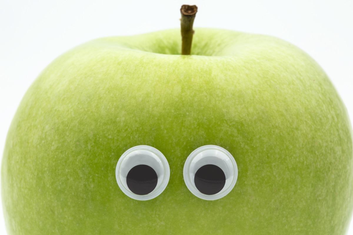 Googly eyes on green apple