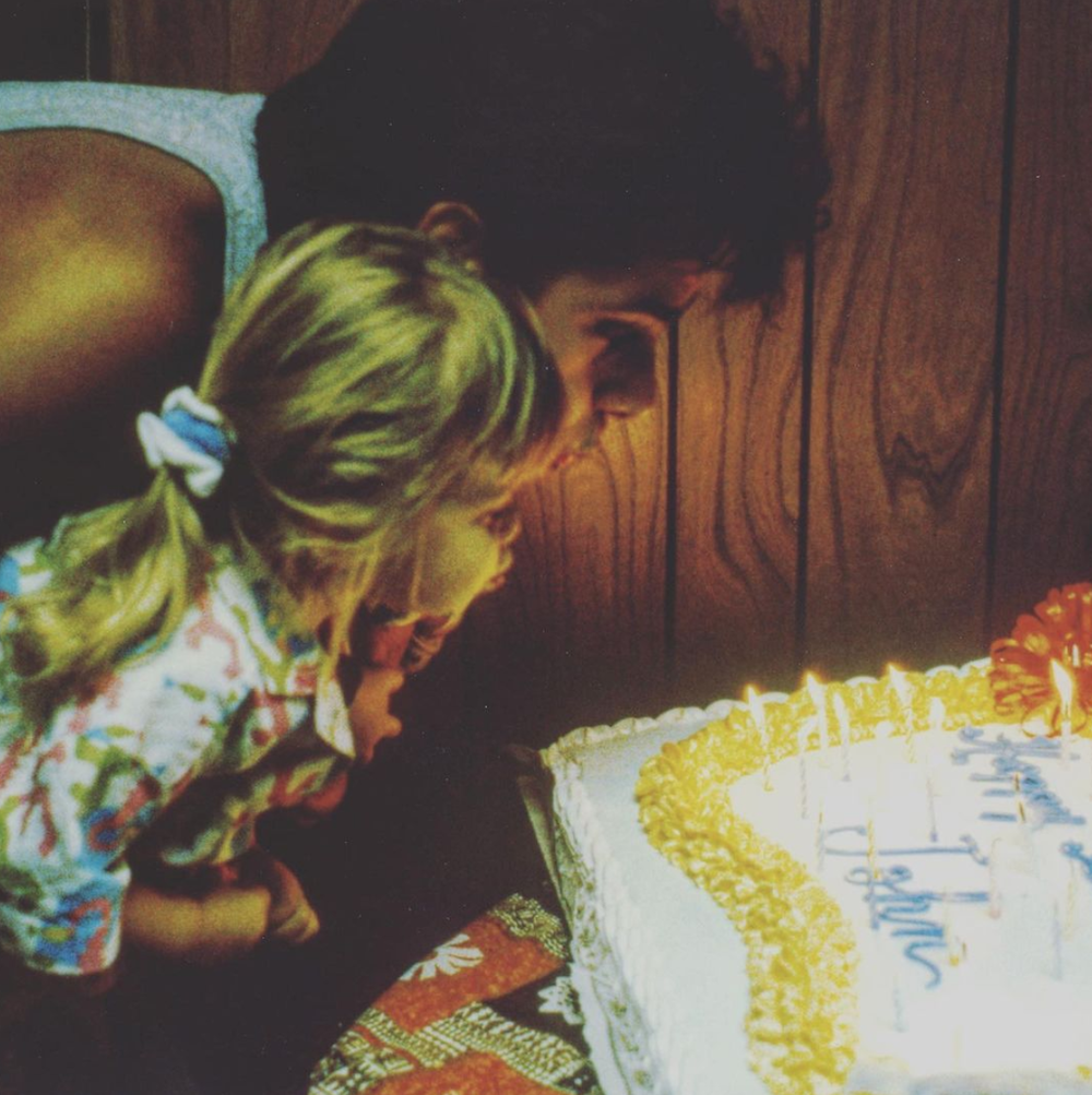 John Stamos blowing out candles on a birthday cake while holding one of the Olsen twins