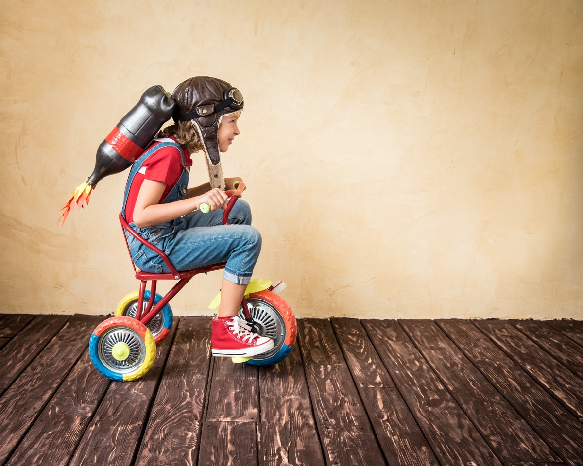 Kid wearing homemade jetpack and sitting on tricycle