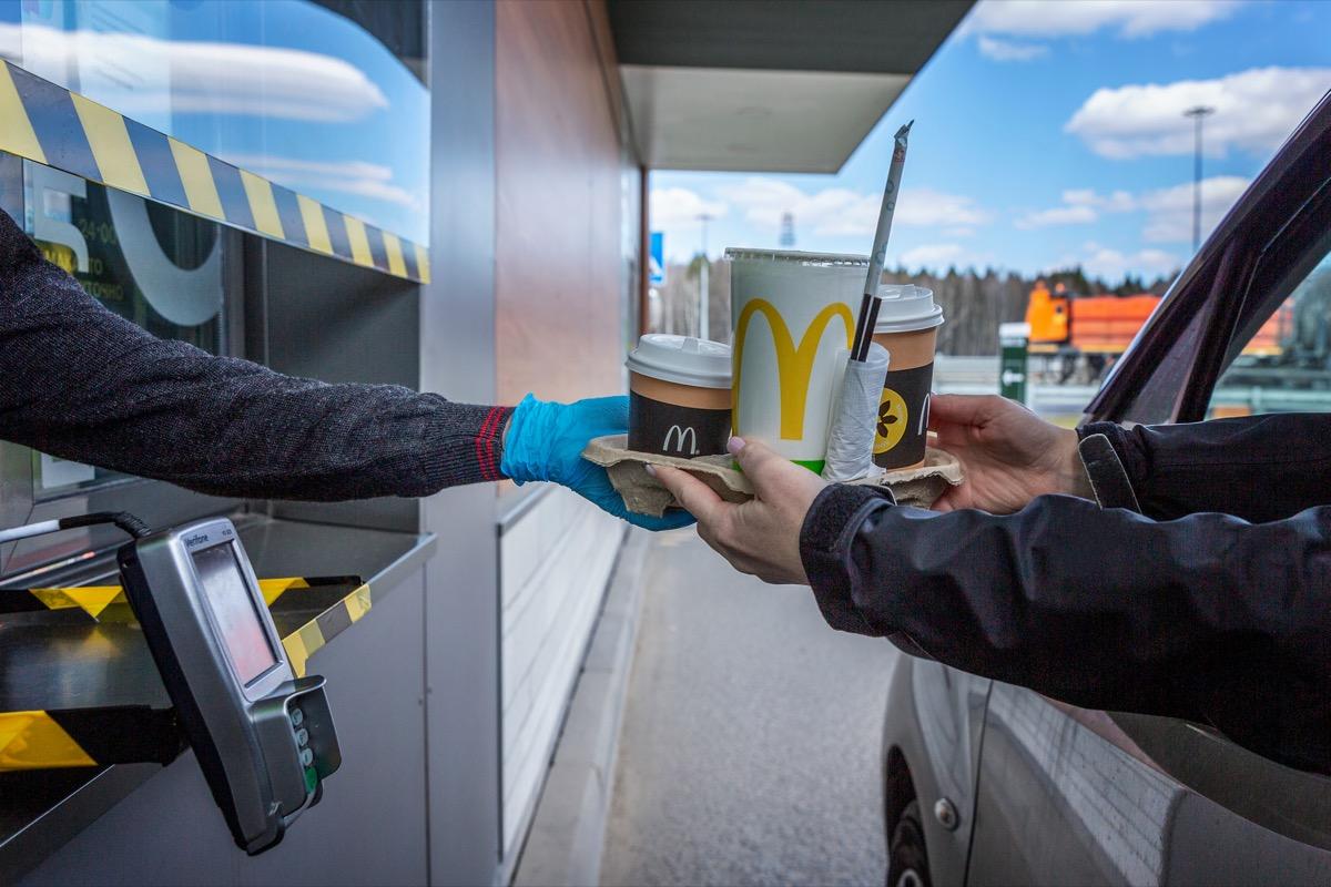 Worker handing order through window at McDonald's drive-thru