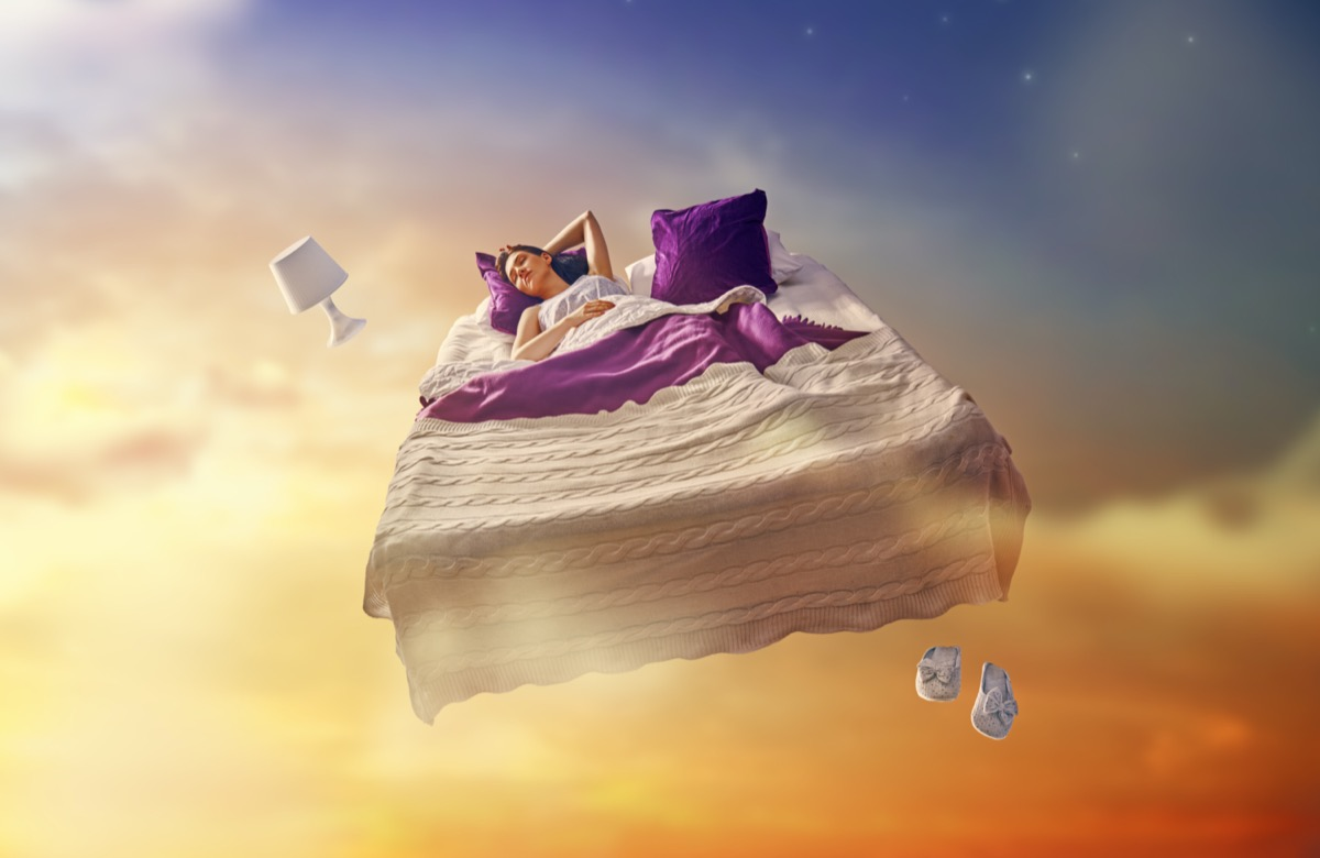Sleeping woman in bed floating through a starry sky