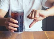 Person holding glass of soda and give it a thumbs down