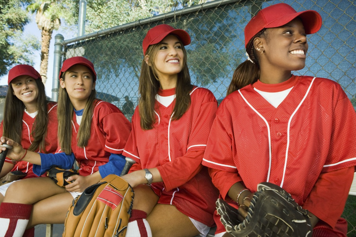Young women on softball team sitting in dugout