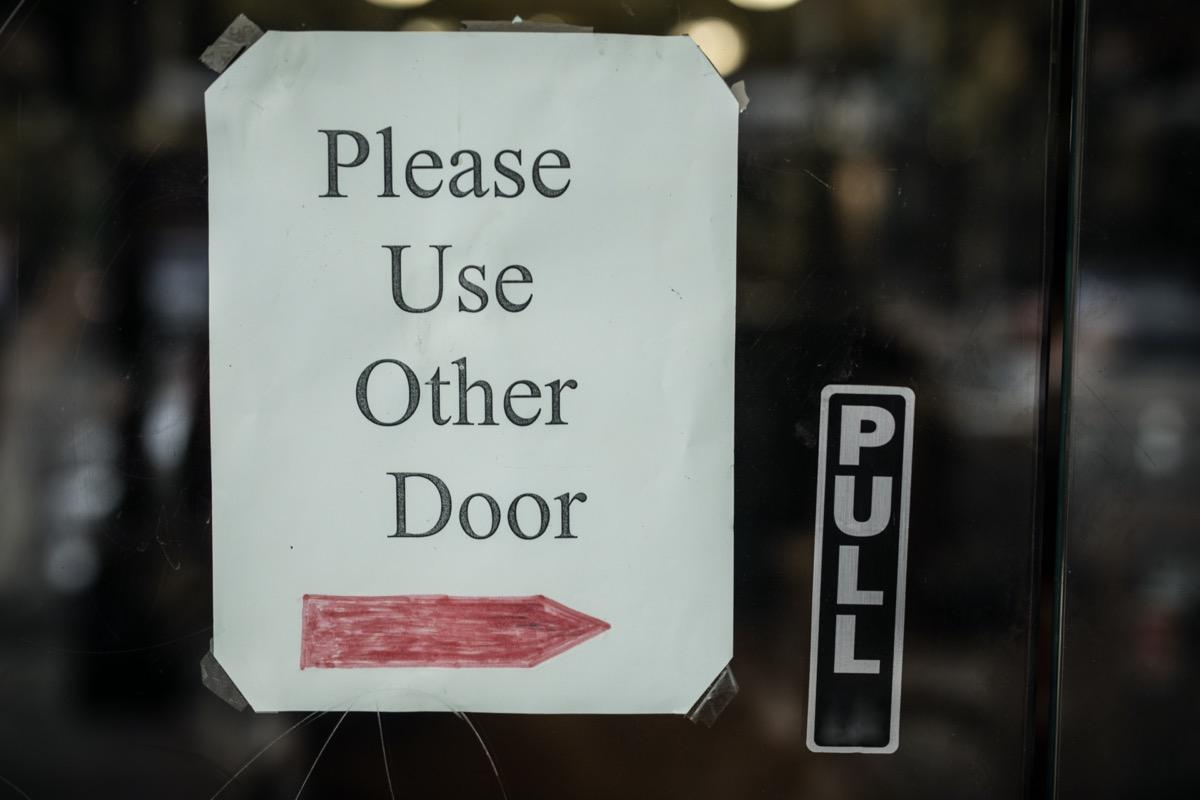 """""""Please Use Other Door"""" sign on glass door"""