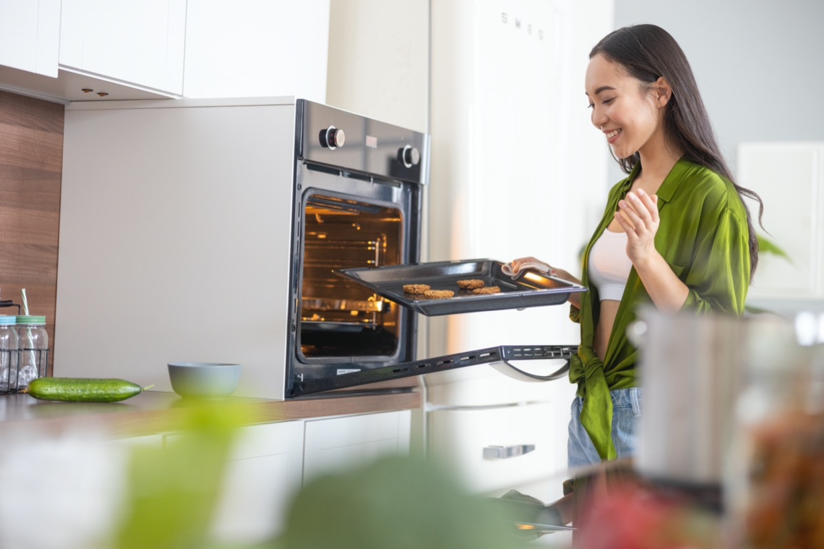 Young woman putting tray of cookies in oven