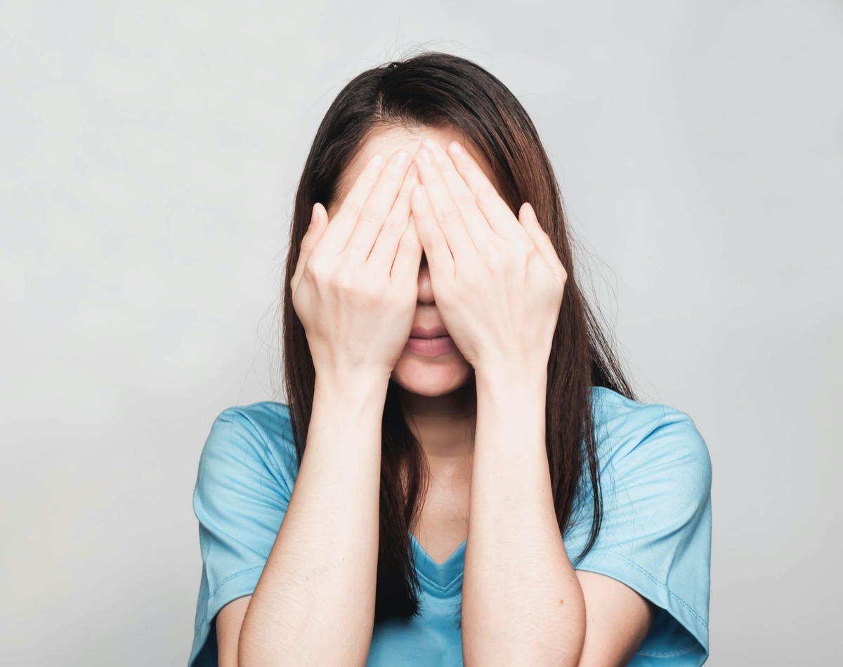Woman covering eyes with her hands