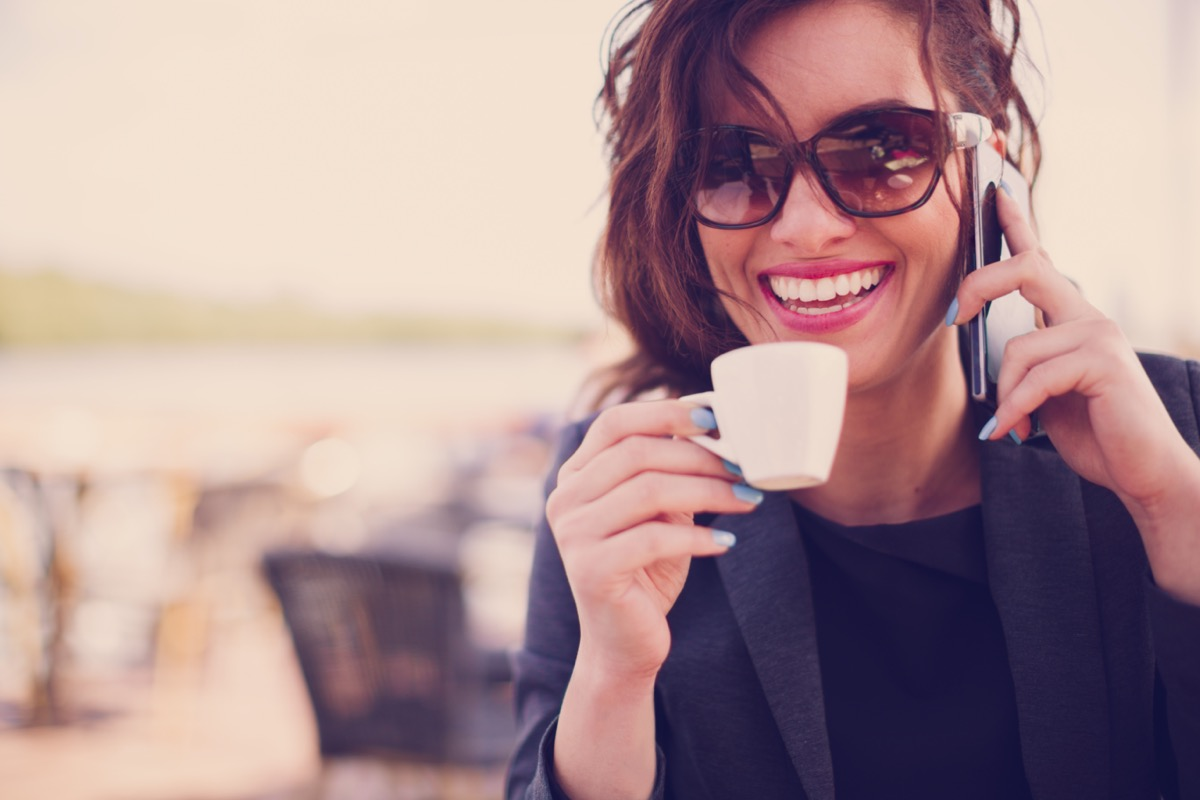 Woman drinking espresso and talking on the phone