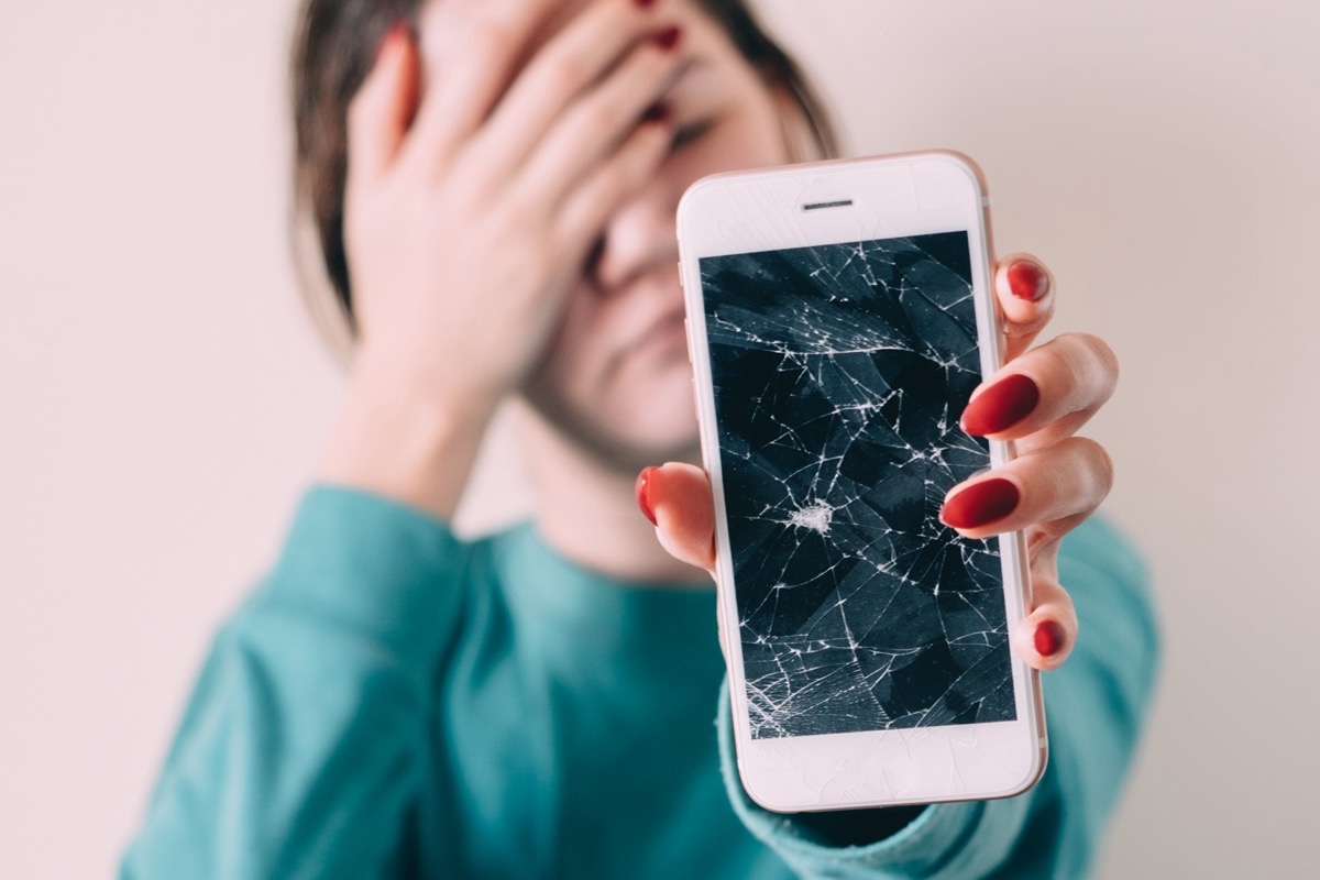 Woman holding out phone with cracked screen
