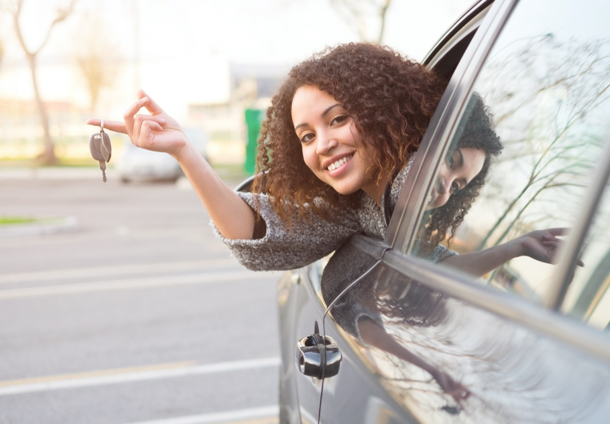 Woman leaning out of new car holding keys