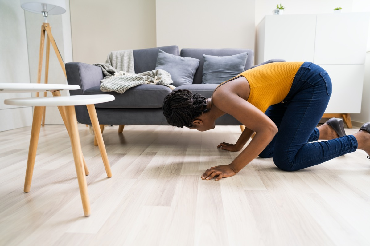 Woman looking under couch for lost item