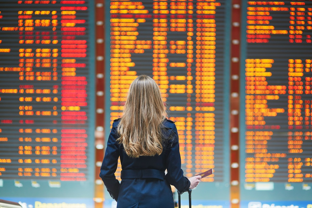 Woman standing in front of departures board at airport