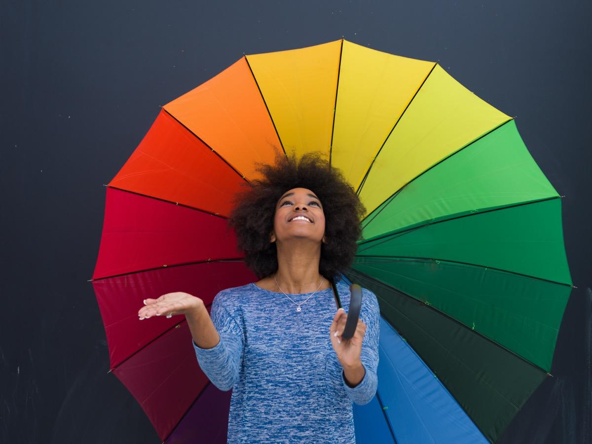 Young woman holding rainbow umbrella