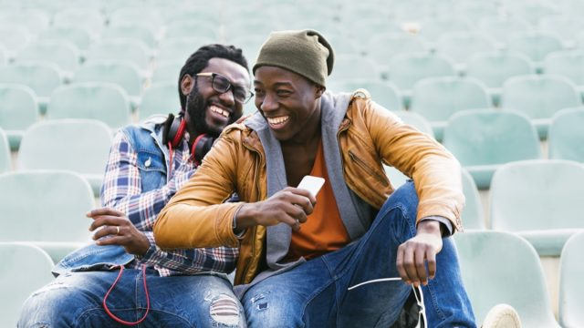 Two young male friends sitting in empty stadium seats laughing