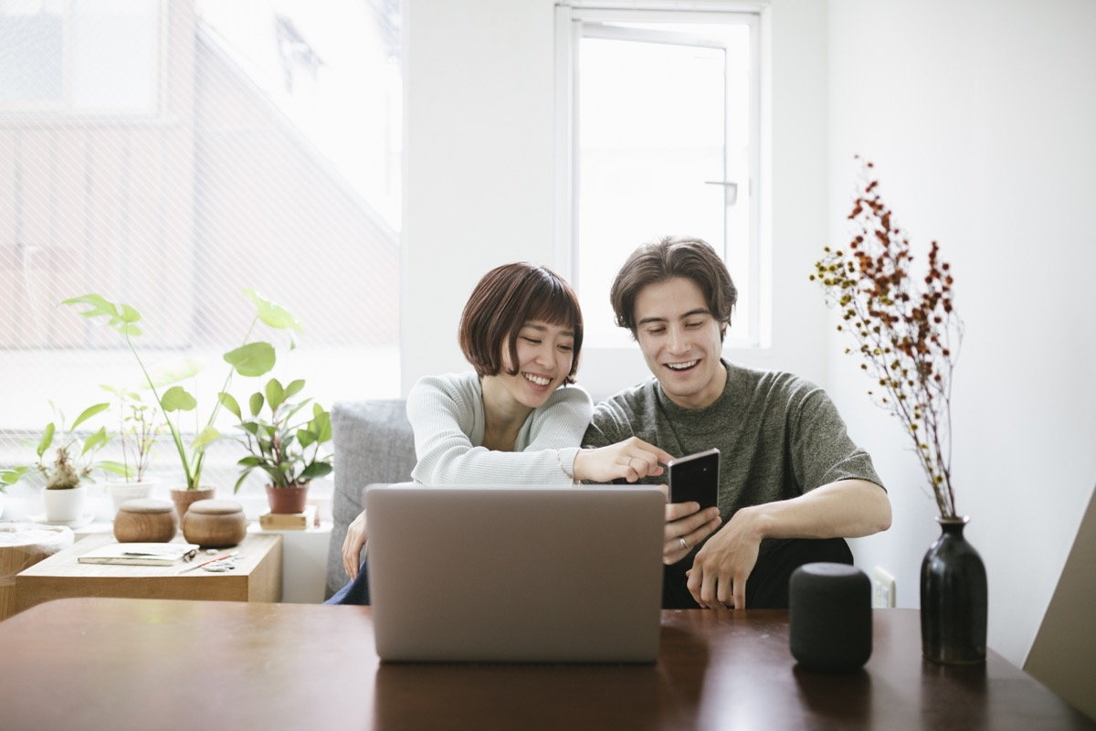 Couple sitting behind a coffee table, installing virtual assistant.