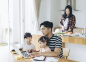 Father with two children using laptop to work from the living room.