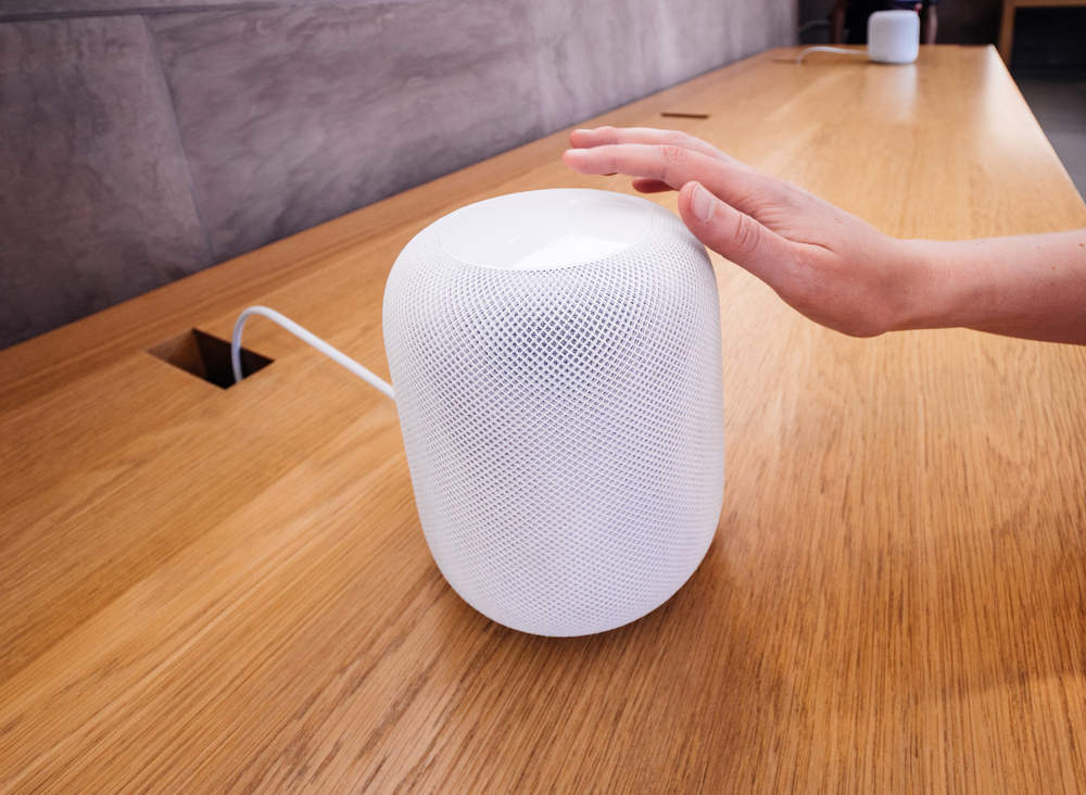 A hand activates a white Apple HomePod that is being displayed in the Apple Store.