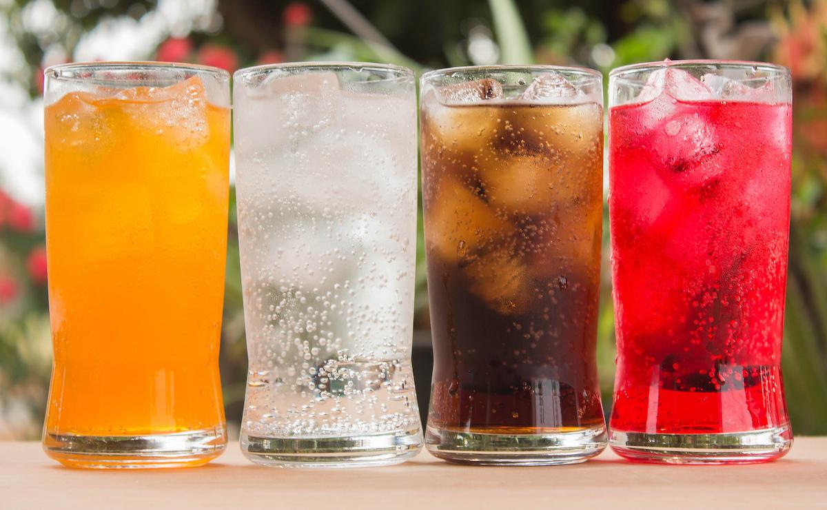 orange soda, seltzer, soda, red soda on wood table in glasses