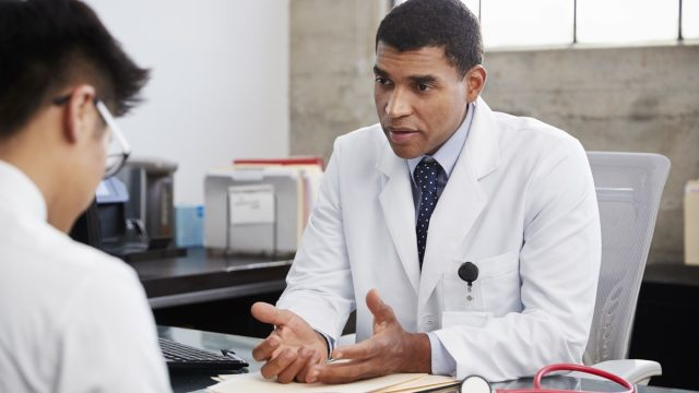 Concerned male doctor counselling male patient