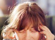 Mature woman touching temples, Migraine concept