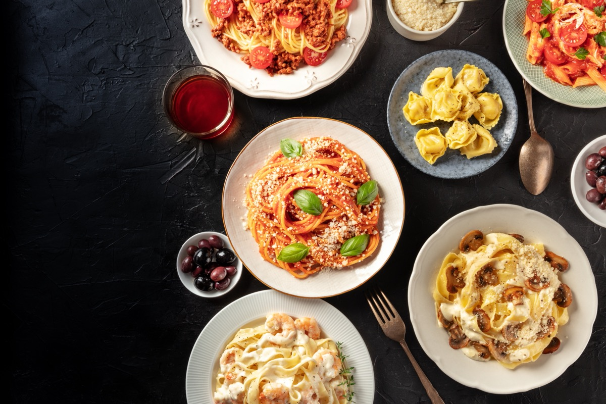 bowls of different kinds of pasta on black table