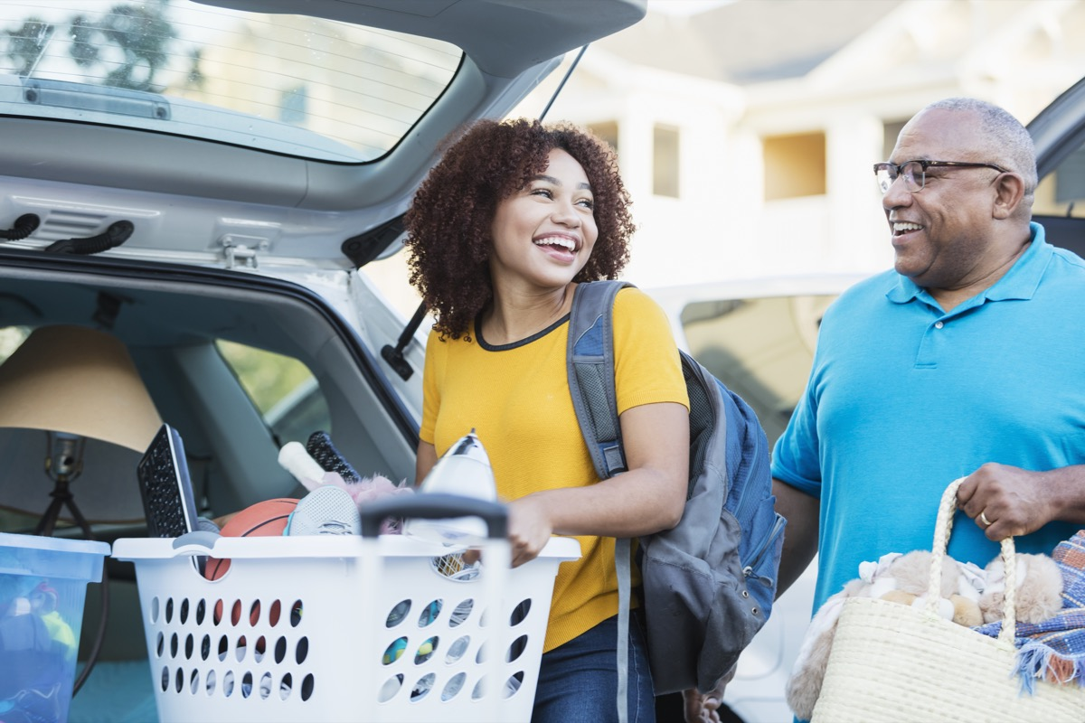 man helping his daughter relocate, perhaps into an apartment or college dorm. They are in a parking lot unloading their cars. The young woman is carrying a laundry basket filled with her belongings.