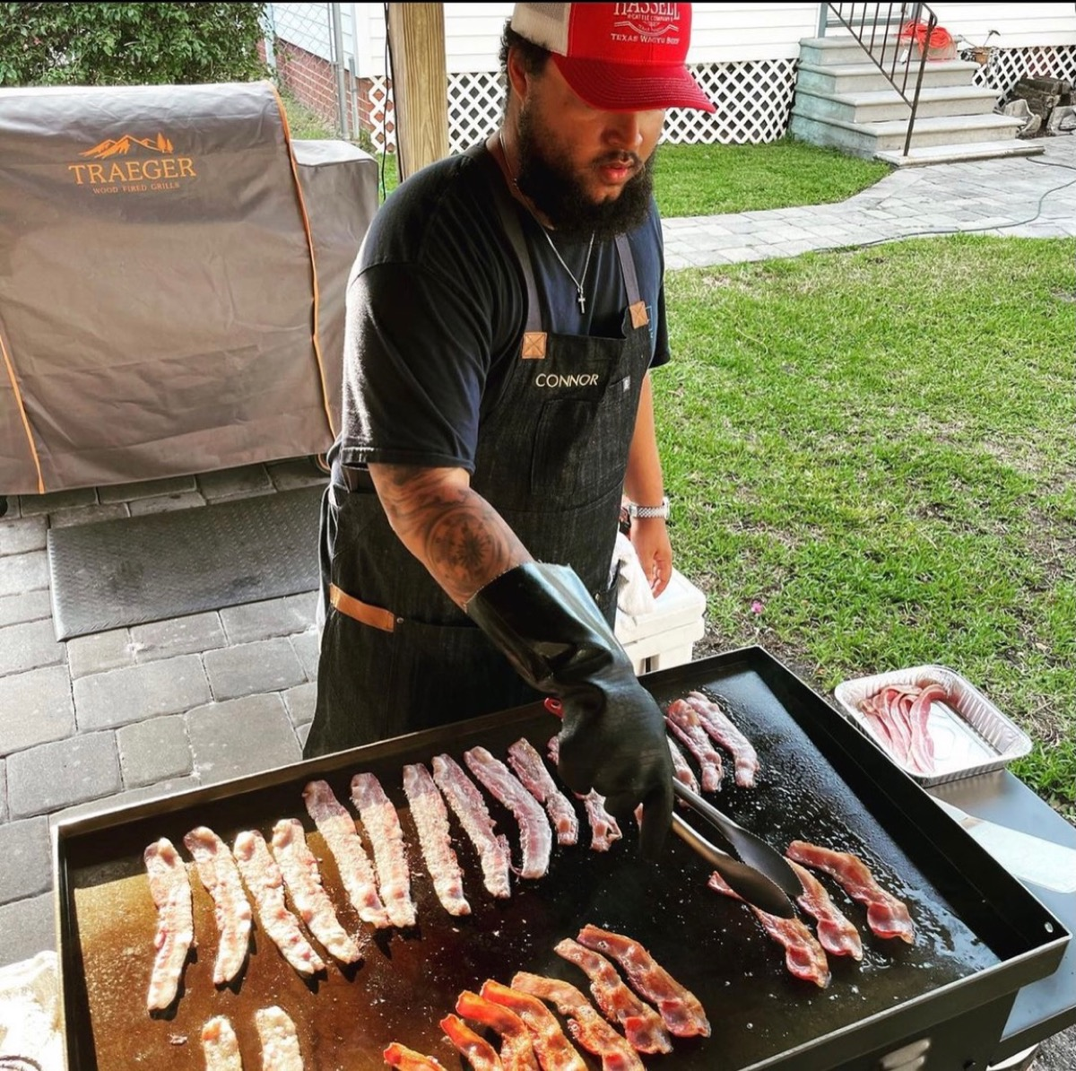 connor cruise in red and white hat grilling meat