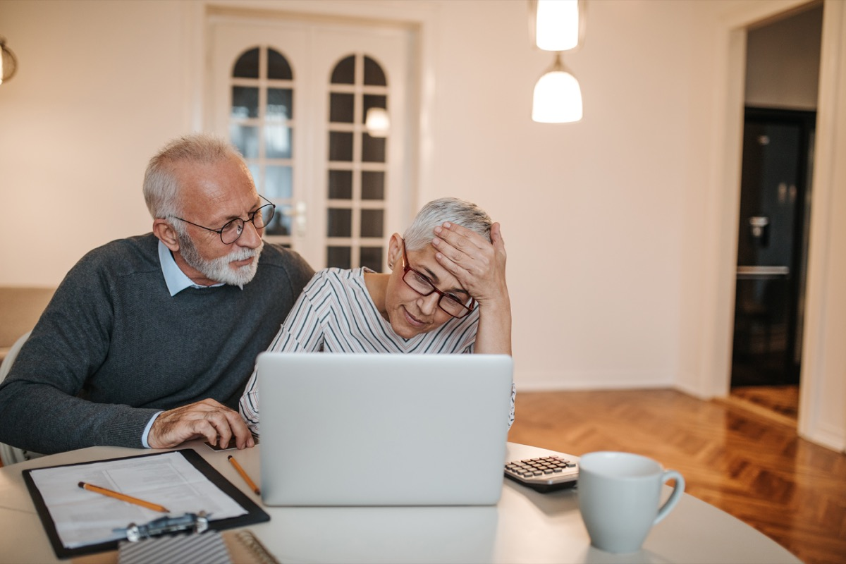 Mature couple calculating finances at home.