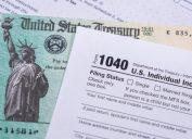A stimulus check sitting underneath a 1040 tax form