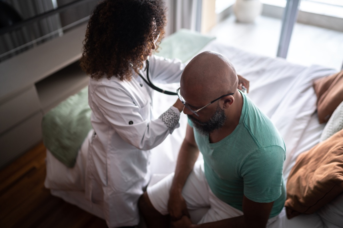 Doctor listening to patient's heartbeat during home visit
