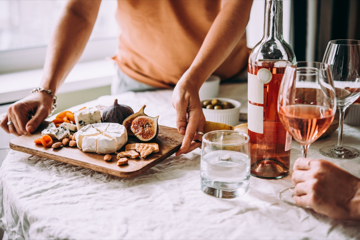 friends sharing some wine, fruit, and cheese at a dinner party