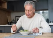Portrait of a happy man at home eating a healthy salad – nutrition concepts