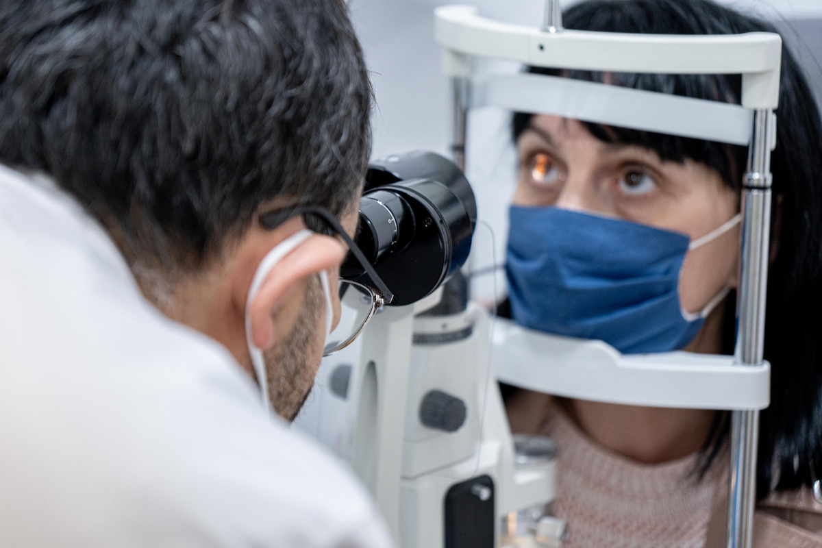 Optician examining woman's eyes