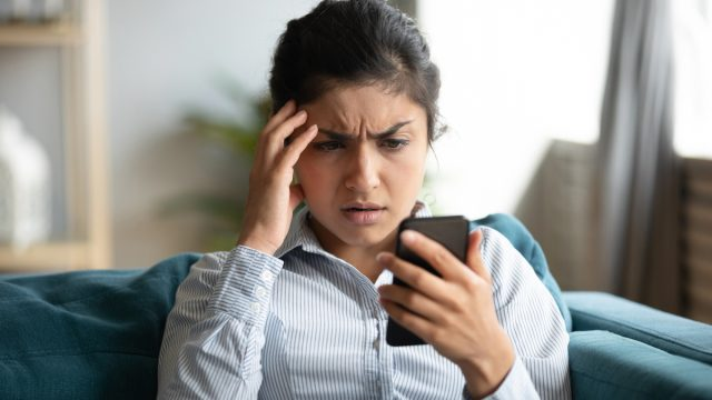 Confused young woman at home looking at cellphone having operational problems