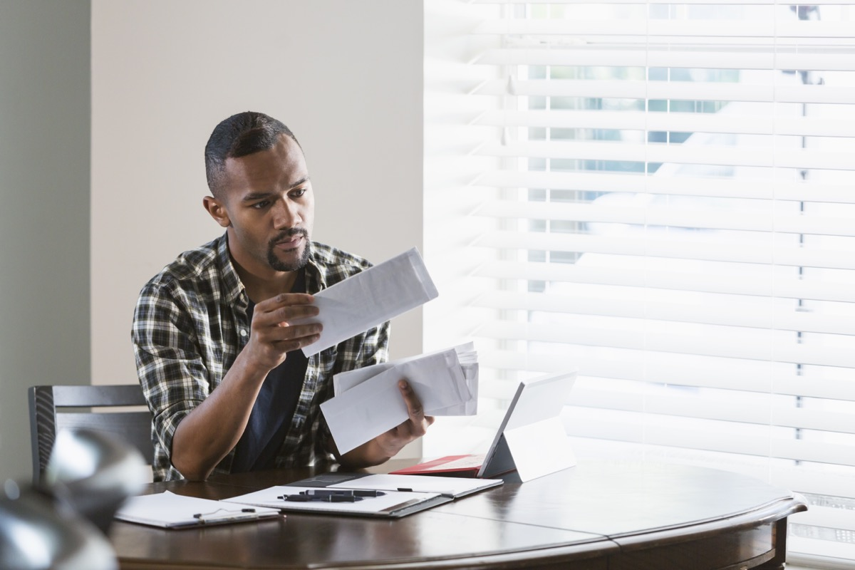 man sitting at a desk by a window at home, paying bills. He is looking through a stack of envelopes and has his laptop computer in front of him.