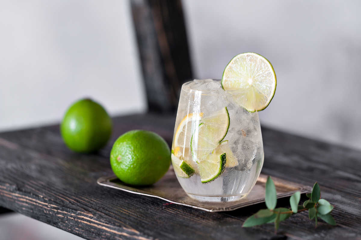 gin and tonic with limes on vintage background