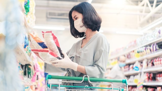 woman wearing face mask and rubber glove in supermarket looking at snacks