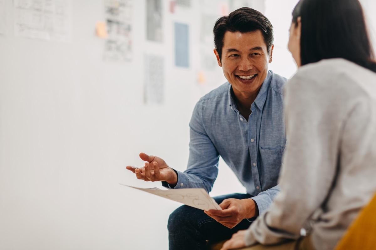 raphic designer sharing ideas during meeting in modern office studio
