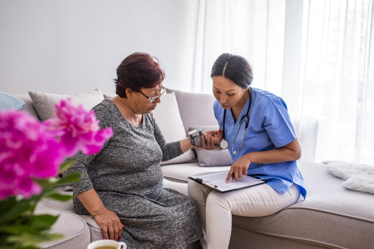 nurse doing blood pressure monitoring for senior woman at home
