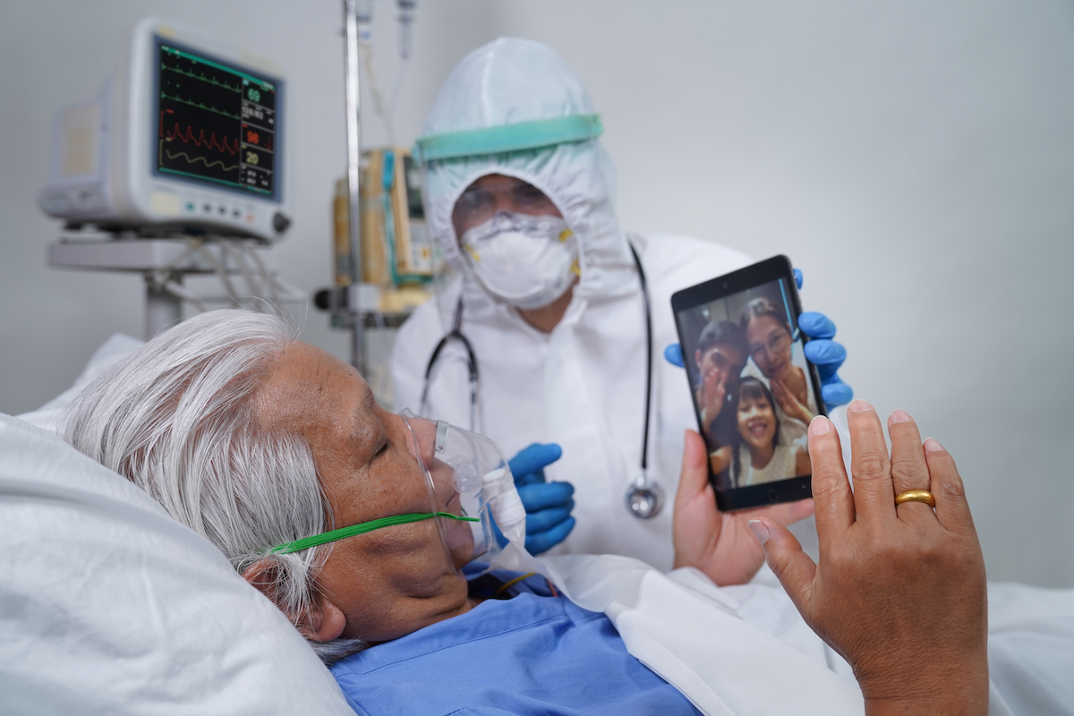 Doctor helps elderly coronavirus patient in the hospital, communicating with his family using tablet video call.