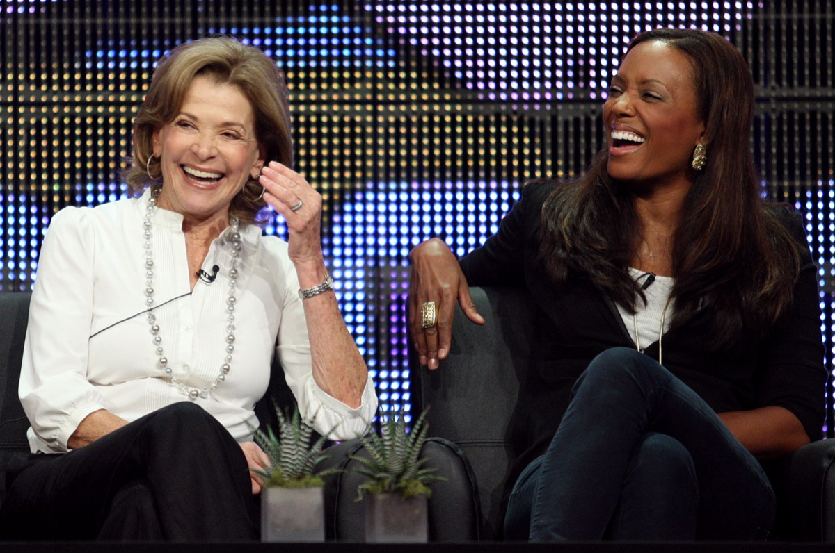 jessica walter in a white top and black pants laughing with aisha tyler in a black and white outfit, both seated