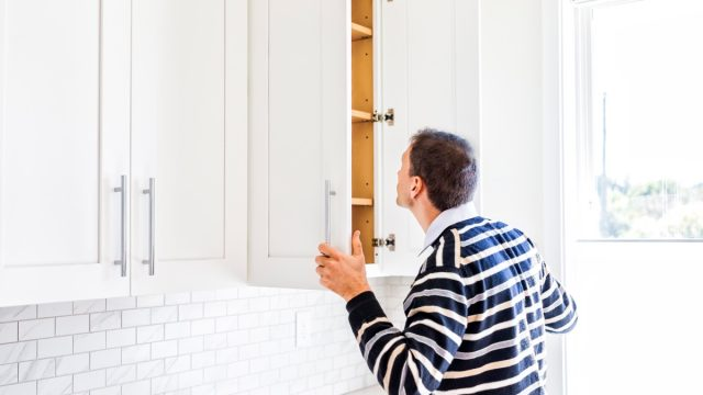 Man looking in kitchen cabinet