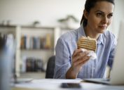 Woman working from home and eating a sandwich for lunch at her laptop