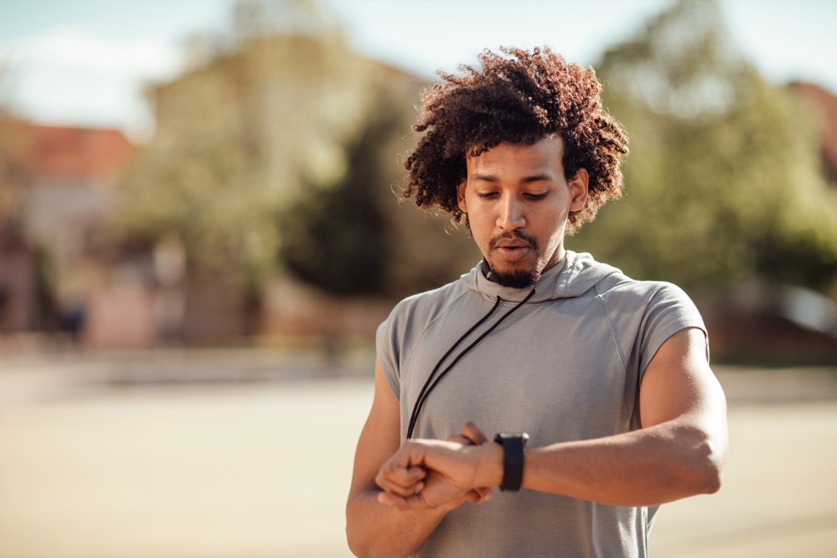 Young sportsman looking at fitness tracker