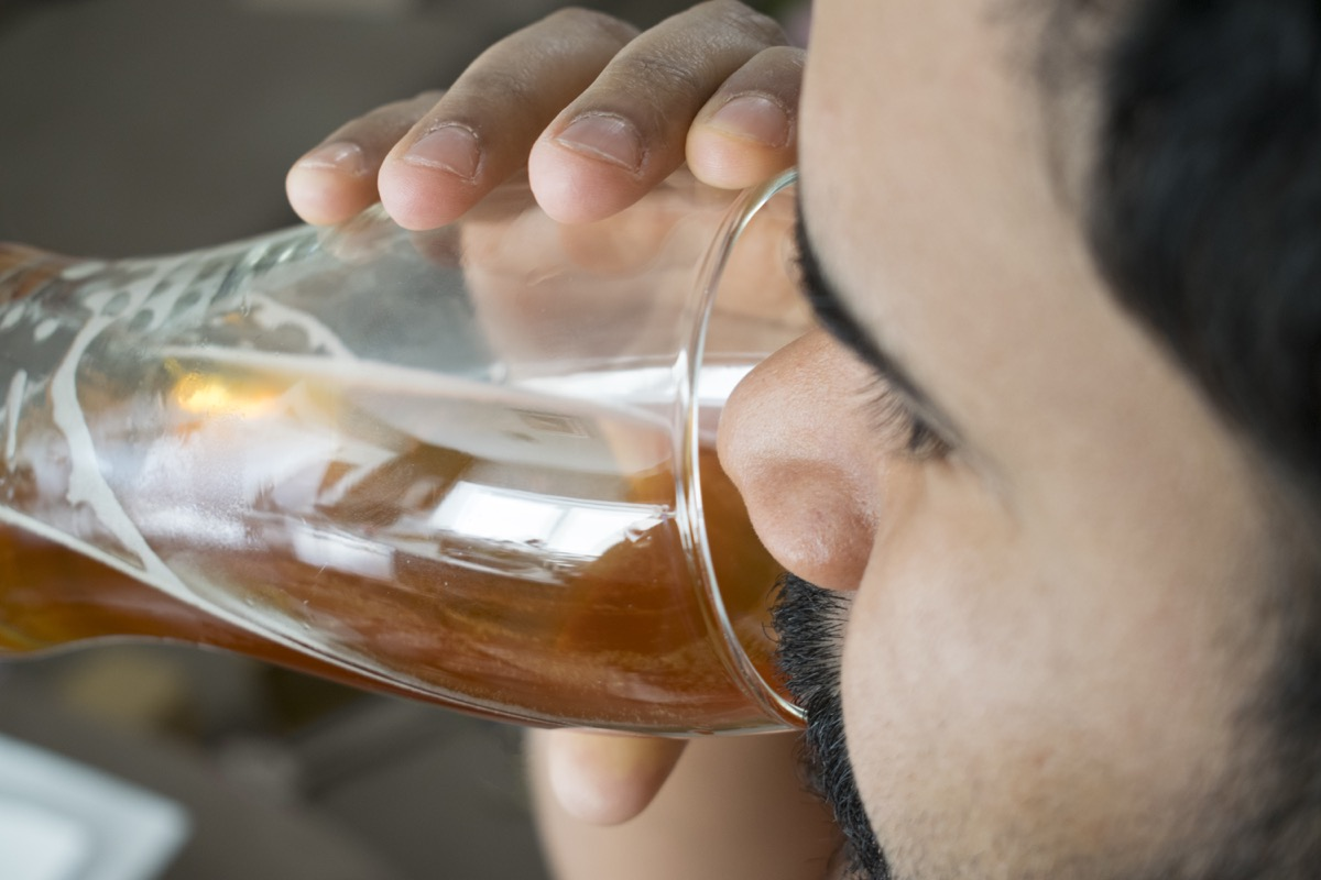 bearded man drinking a glass of light beer.