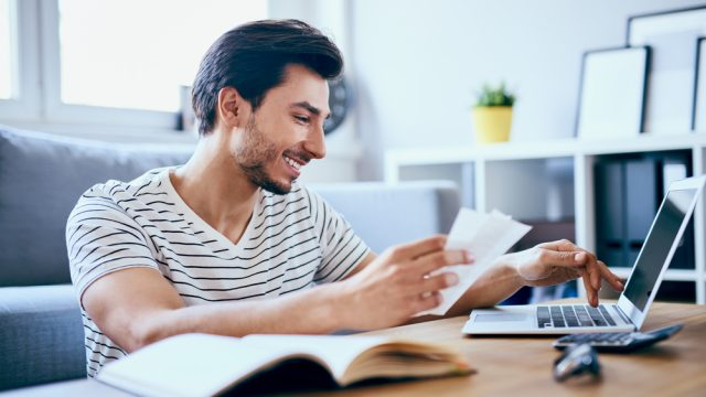 A young man filing taxes on his laptop while smiling and maybe cashing his COVID stimulus check
