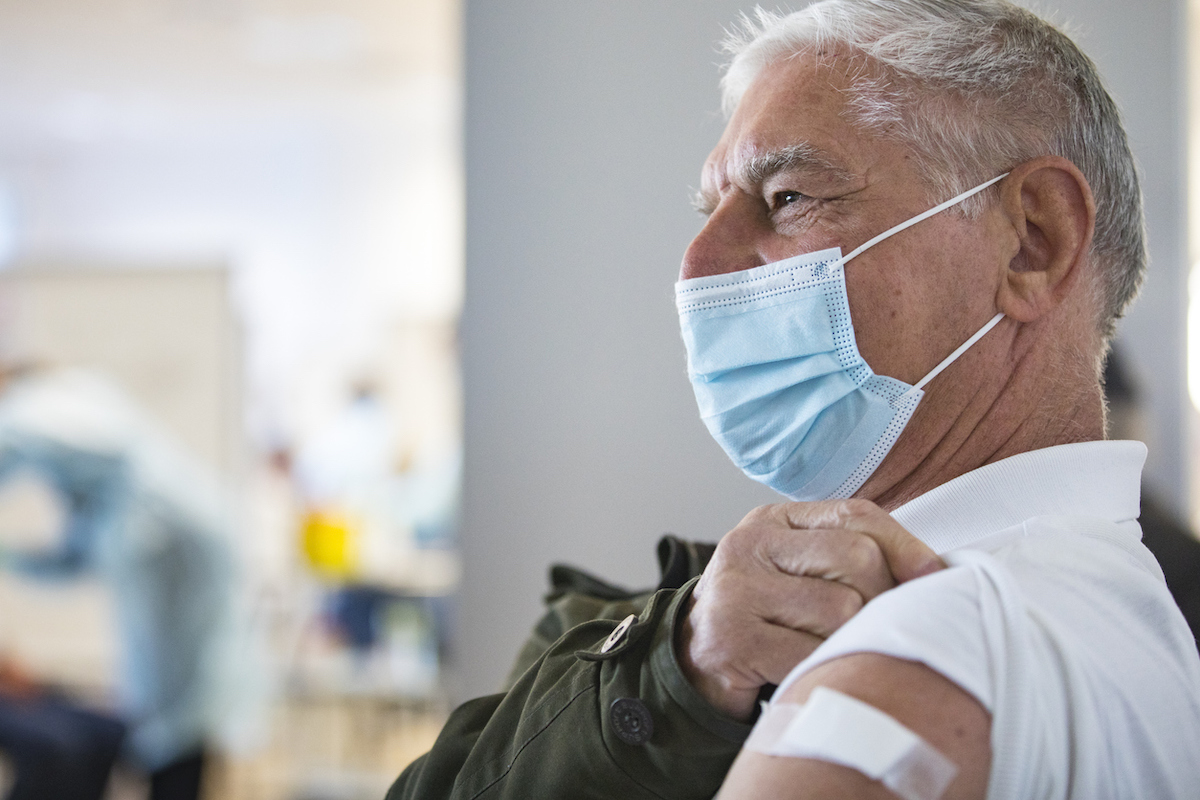 Senior Adult Man Sitting and Waiting in Field Hospital after Receiving COVID-19 Vaccine.