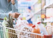 man grocery shopping with full cart